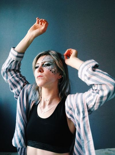 Young woman with face paint and arms raised looking away at home