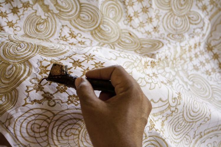 Close-up of hand holding canting. canting is tool to mke batik