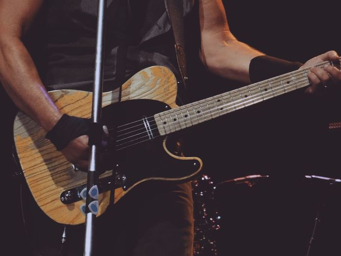 Midsection of man playing guitar during concert