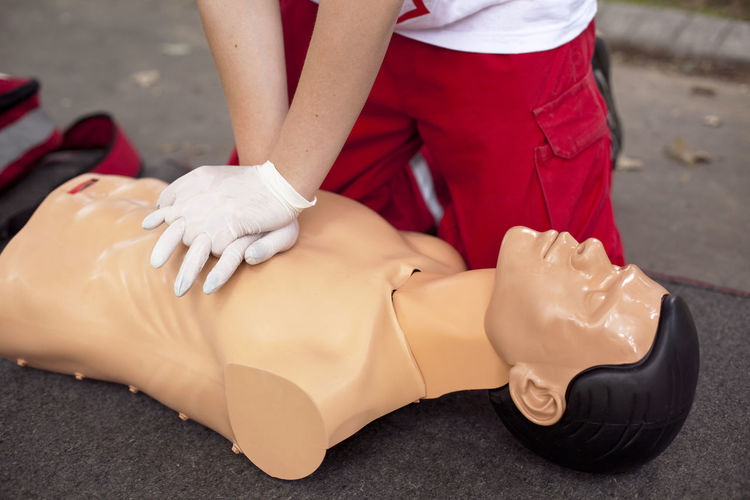 Low section of woman applying cpr on dummy