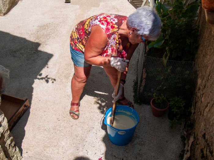 High angle view of woman mixing liquid in bucket on footpath