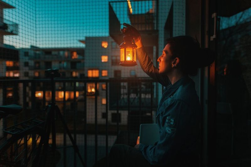 Side view of woman holding oil lamp while sitting in balcony at dusk