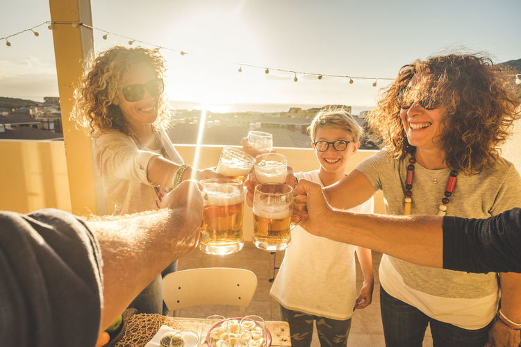 Group of friends clinking all together having fun in friendship outdoor on the rooftop terrace with city and sea view during summer dinner at the sunset at home - vacation and enjoying lifestyle Food And Drink Drink Group Of People Alcohol Refreshment Young Adult Adult Friendship Young Women Happiness Emotion Smiling Sunlight Togetherness Nature Glasses Sky Beer - Alcohol Lens Flare Glass Celebratory Toast Drinking Beer Glass Hairstyle Child