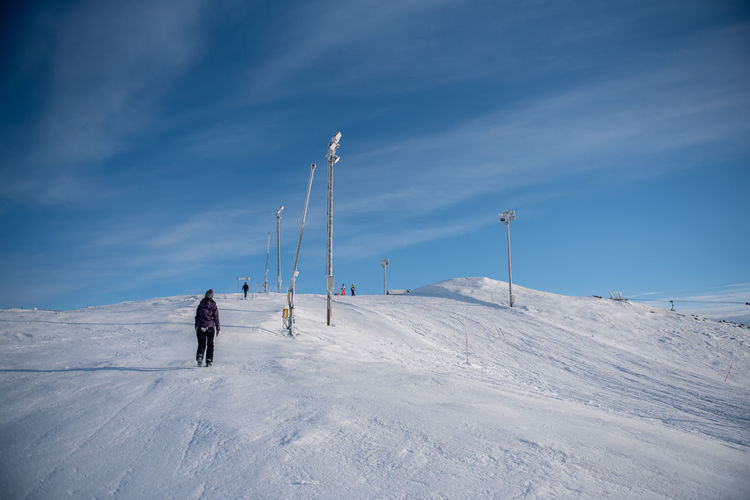 Rear view of person walking on snow covered field against sky