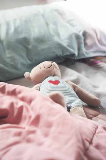 Midsection of baby resting on bed at home