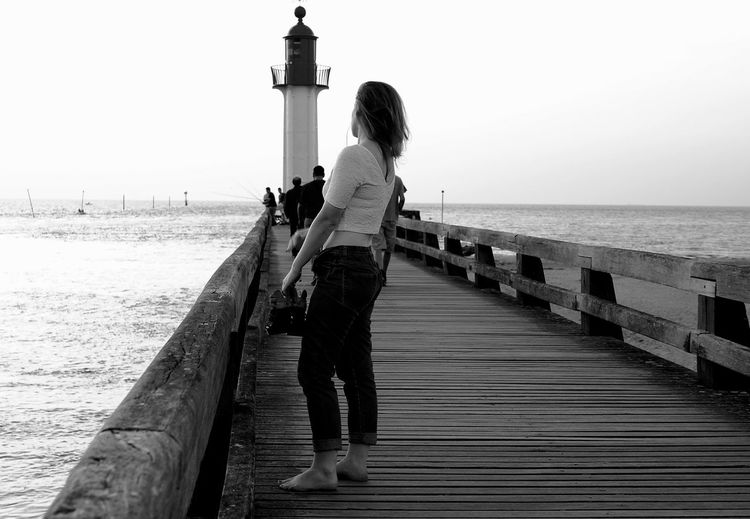Side View Of Woman Standing On Pier Against Lighthouse By Sea