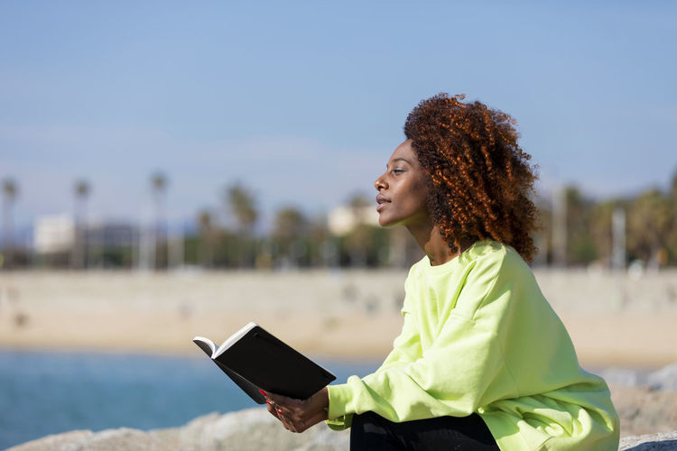 Side view of a young curly afro woman sitting on a breakwater holding a book while smiling and looking away outdoors One Person Curly Hair Young Adult Women Technology Wireless Technology Young Women Real People Focus On Foreground Adult Hairstyle Communication Day Looking Hair Three Quarter Length Nature Waist Up Standing Beautiful Woman Outdoors Woman African American Afro Denim Happiness Happy Fun Daylight Sunlight