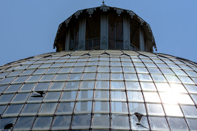 Low angle view of glass building against clear blue sky