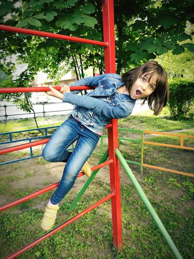 Portrait of girl playing on outdoors play equipment in playground