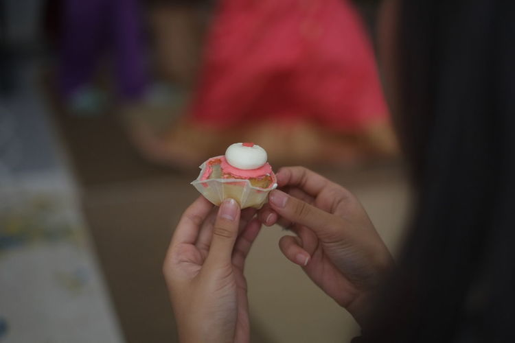 Close-up of hand holding cup cake