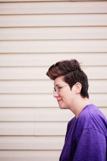 Smiling Woman Wearing Eyeglass Against Wall