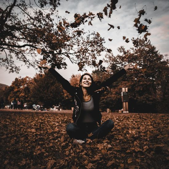 Smiling young woman with arms raised throwing autumn leaves while sitting on field in park