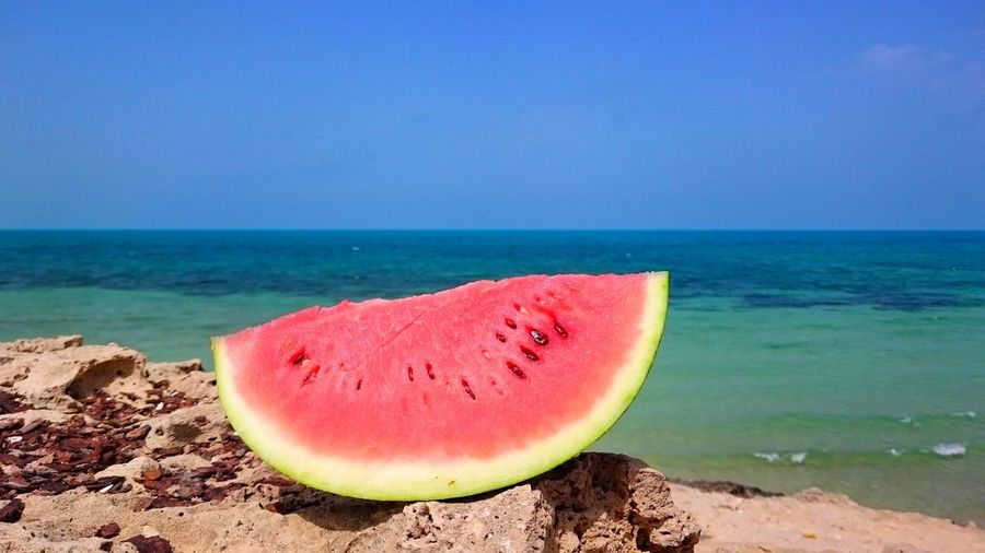 Close-up of watermelon slice on rock against blue sky