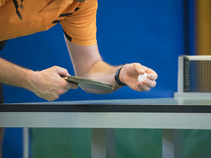 Table Tennis Player serving Tennis Ball Blue Body Part Day Effort Focus On Foreground Hand Holding Human Body Part Human Hand Lifestyles Men Midsection One Person Outdoors Playing Real People Sport Standing Table Table Tennis
