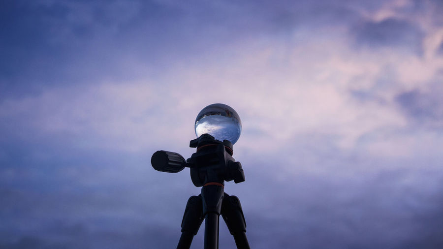 Low angle view of person photographing against sky