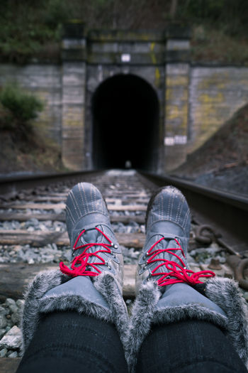 Low section of person wearing winter boots sitting on railroad track