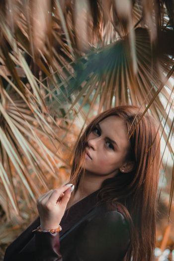 Portrait of beautiful young woman by palm leaf