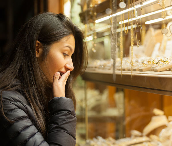 Side view of shocked woman looking towards jewelry in shop