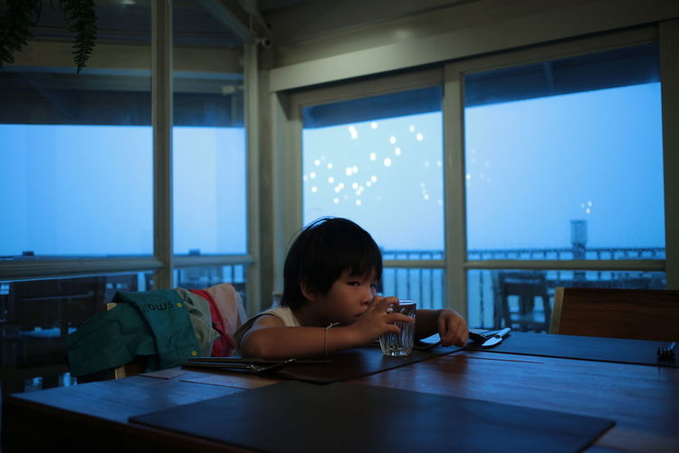 Childhood Child Table Boys Males  Men Indoors  One Person Headshot Real People Sitting Portrait Window Casual Clothing Day Holding Technology Innocence Directly Above Dinner