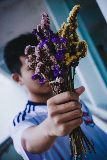 Portrait of woman holding purple flower