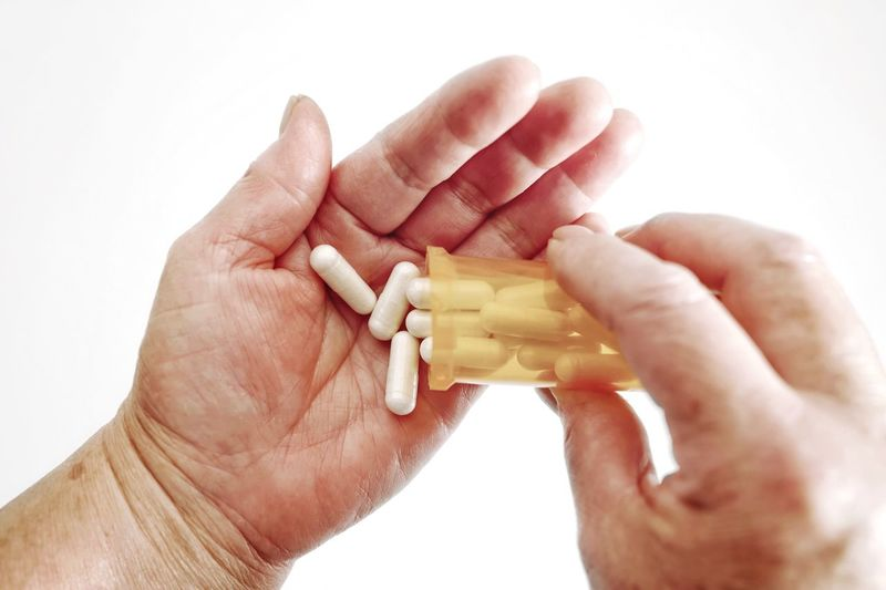 Taking Medicine Healthcare Generic Pills Generic Medicine Hand Capsule Medicine One Woman Only Only Women One Senior Woman Only Senior Women Women Senior Adult Adult Human Hand Hand Human Body Part White Background Holding Healthcare And Medicine Finger Personal Perspective Pill Dose Human Finger