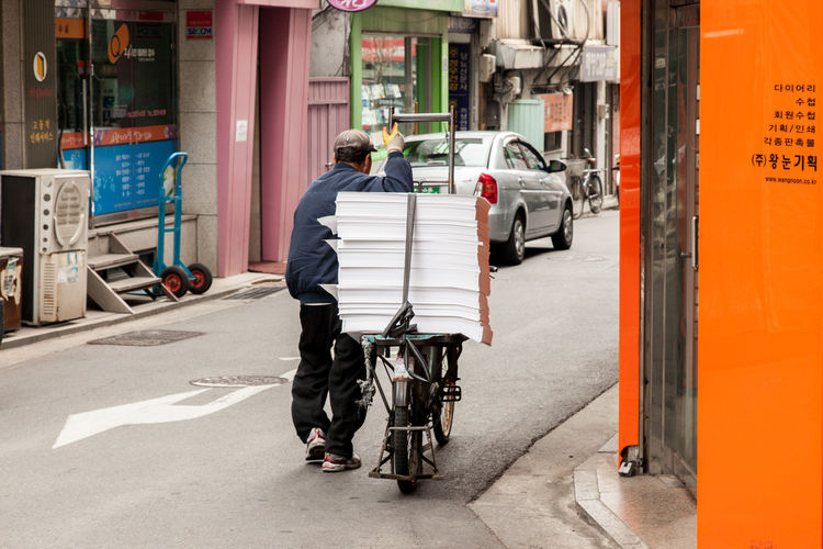 Man With Stacked Bundle Of Paper On Bicycle Over Street