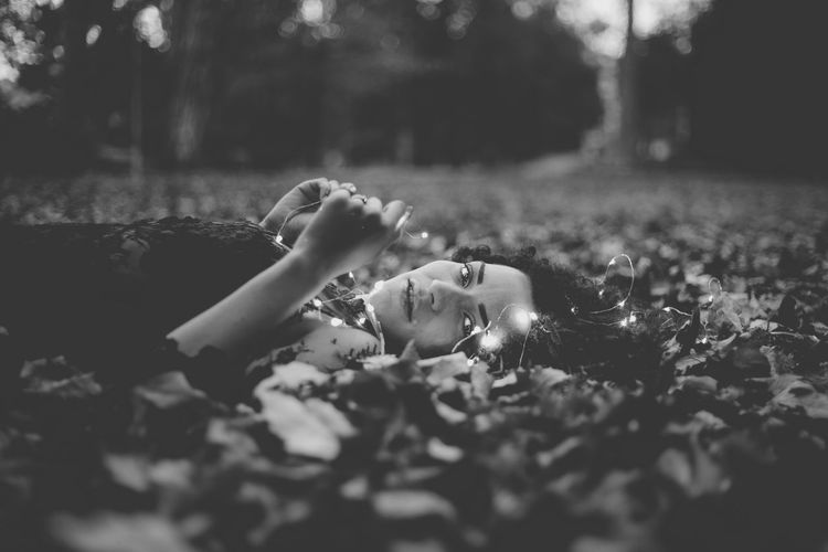 Portrait Of Young Woman Lying On Field At Park During Autumn