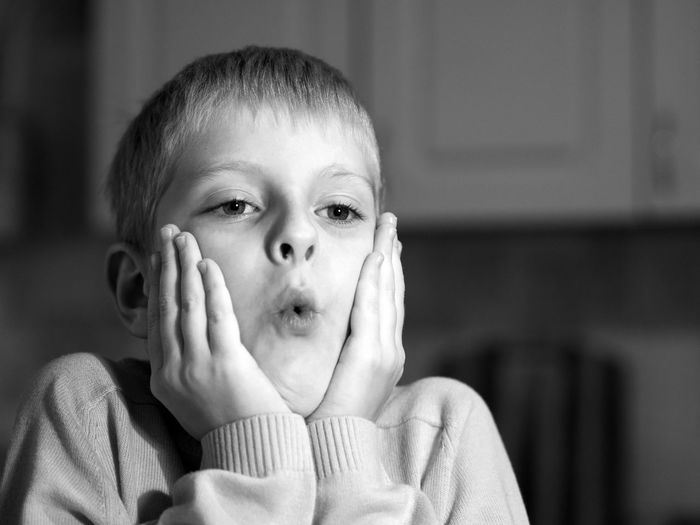Close-up of shocked boy looking away at home