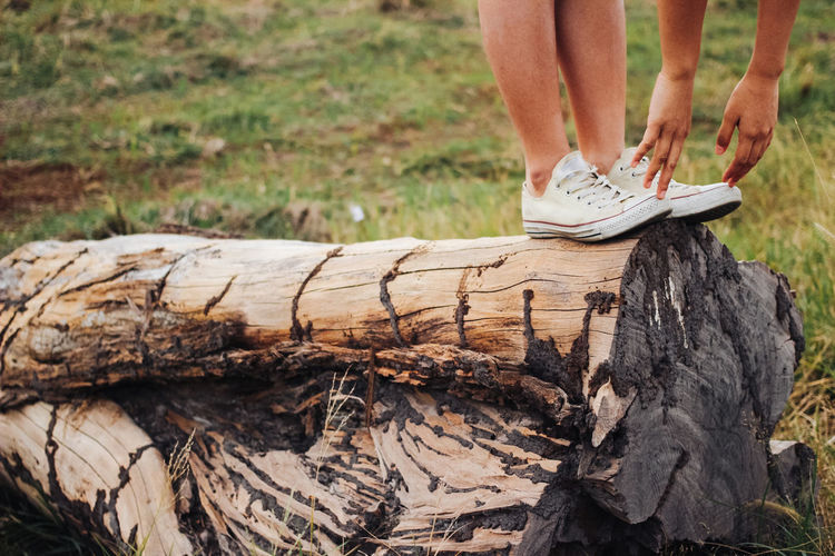 woman legs and hands standing on the wood tree Exercising EyeEm Best Shots Field Tree Woman Close-up Day Grass Hand Human Body Part Human Leg Low Section Nature One Person Outdoors People Real People Shoe Wood - Material
