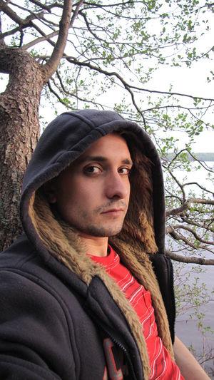 Young Man Wearing Hooded Sweatshirt Relaxing In Park