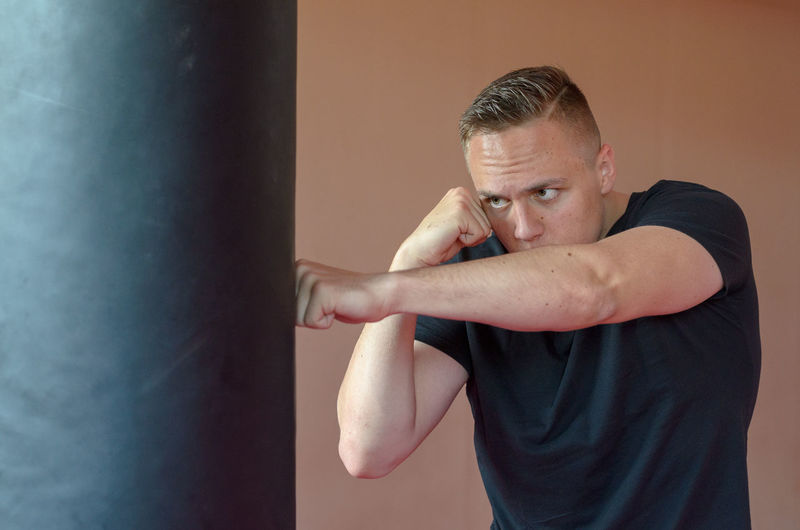 Man hitting punching bag against wall
