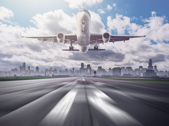 Airplane flying over road against sky
