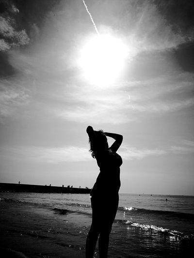 Sensuous woman posing on seashore against sky
