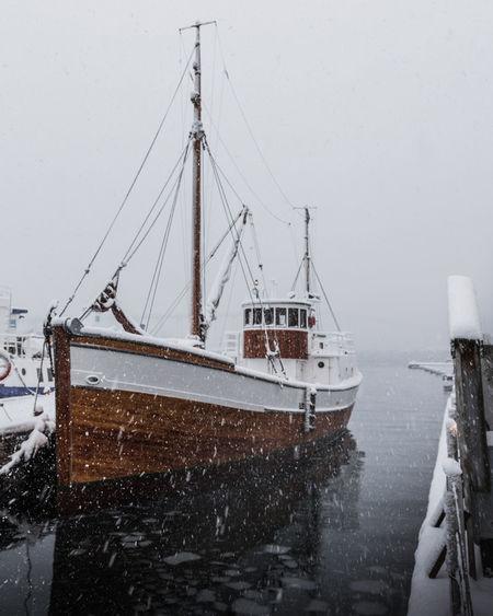 Ship moored in frozen harbor against sky