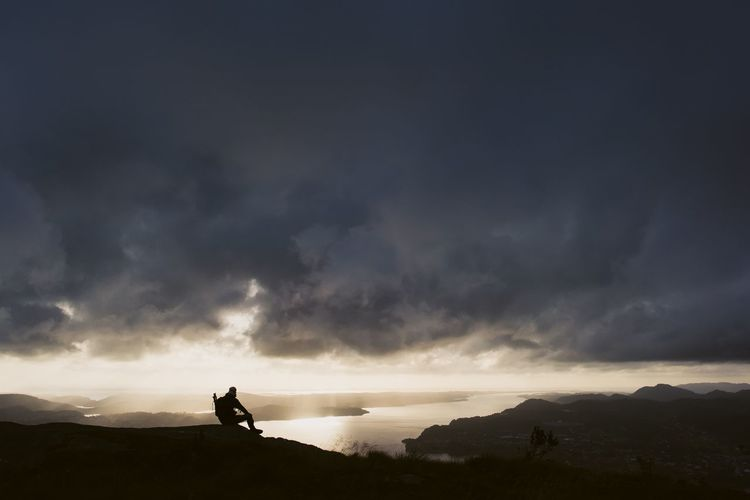 Silhouette Man Sitting On Mountain Against Stormy Clouds During Sunset