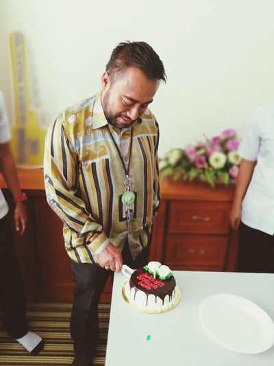 Smiling man cutting birthday cake in office