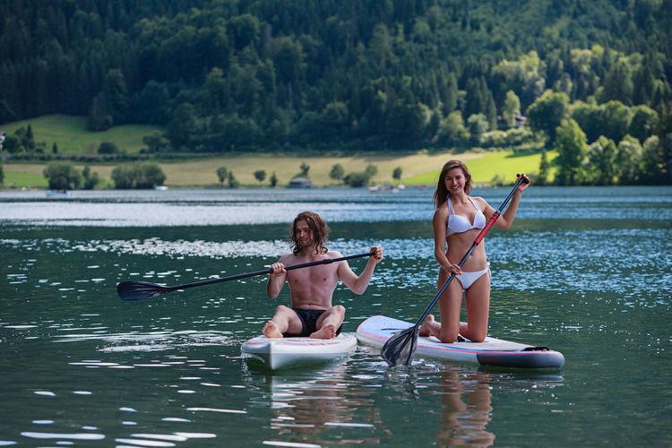 Full length of couple paddleboarding in lake