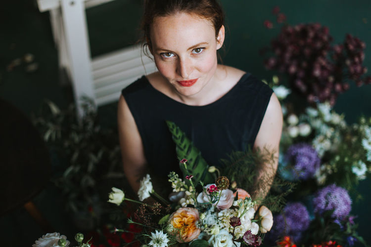 Portrait of smiling woman holding flower bouquet