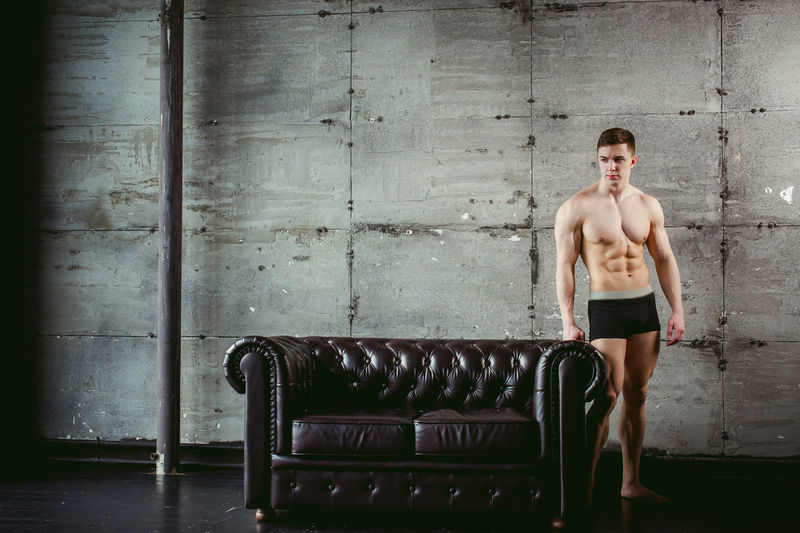 Shirtless muscular man standing by armchair against wall
