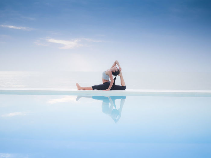 Woman practicing yoga on infinity pool by sea against cloudy sky