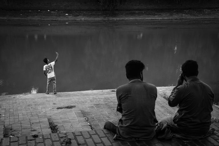 A man was caught on my camera taking a selfie at the Crescent Lake in Dhaka, while others was sitting causally :) Adult Bangladesh Blackandwhite Day Dhaka Leisure Activity Lifestyles Men Outdoors People Real People Rear View Rhsumon Sitting Standing Streetphotography Taking Selfies Togetherness Water