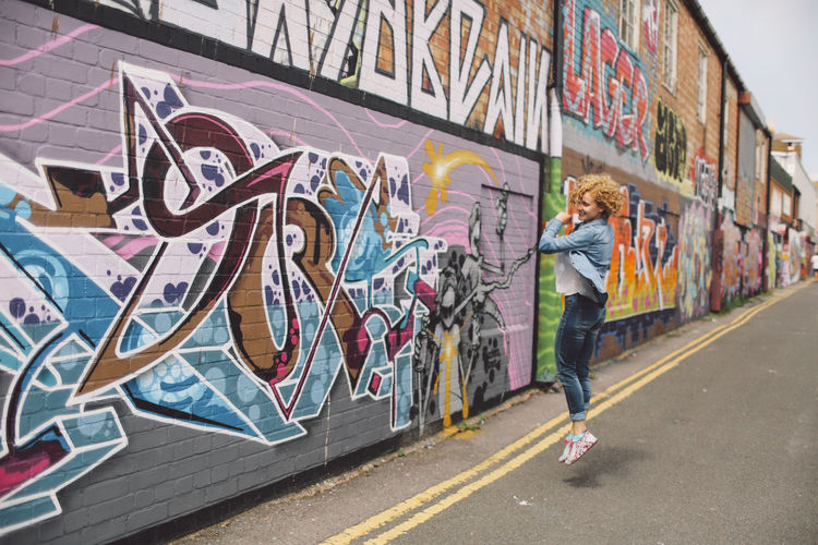 Architecture Art Blonde Brighton Casual Clothing City Curly Hair Downtown Full Length Girl Graffiti In The Air Joy Joyful Jump Leisure Activity Lifestyles Multi Colored Outdoors Play Playful Rotation Street Street Art People And Places