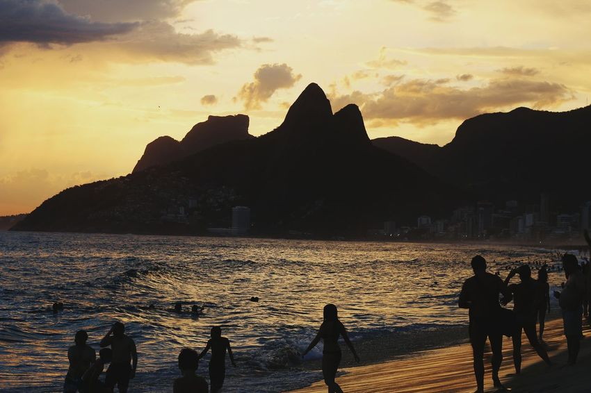 Ipanema Verão 2017 - Rio de JaneiroSunset Mountain Silhouette Travel Vacations Water Nature Beauty In Nature Lake Outdoors Scenics Beach Landscape People Large Group Of People Adult Day