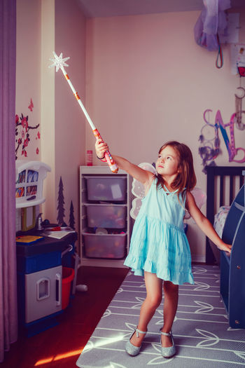 Cute girl wearing angel wings with magic wand standing at home