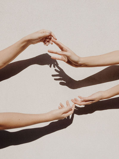Cropped Hands Of Women Against Gray Wall