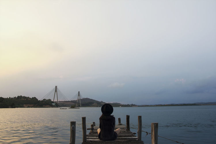Rear view of woman sitting on pier over sea against sky