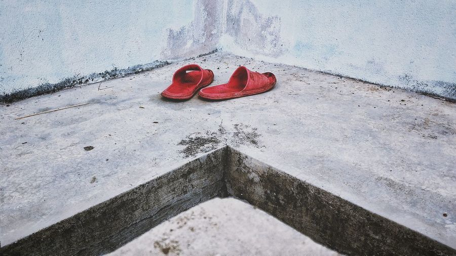 High angle view of shoes on retaining wall
