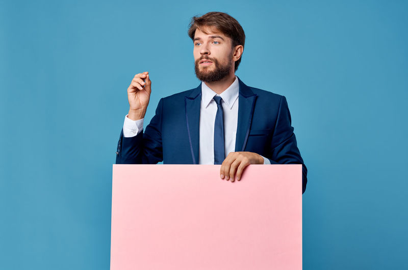 Young man against blue background