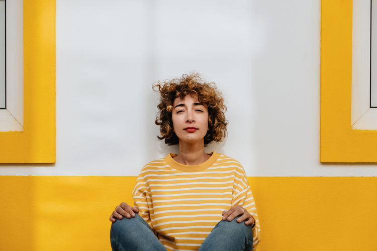 Portrait of woman sitting against yellow wall