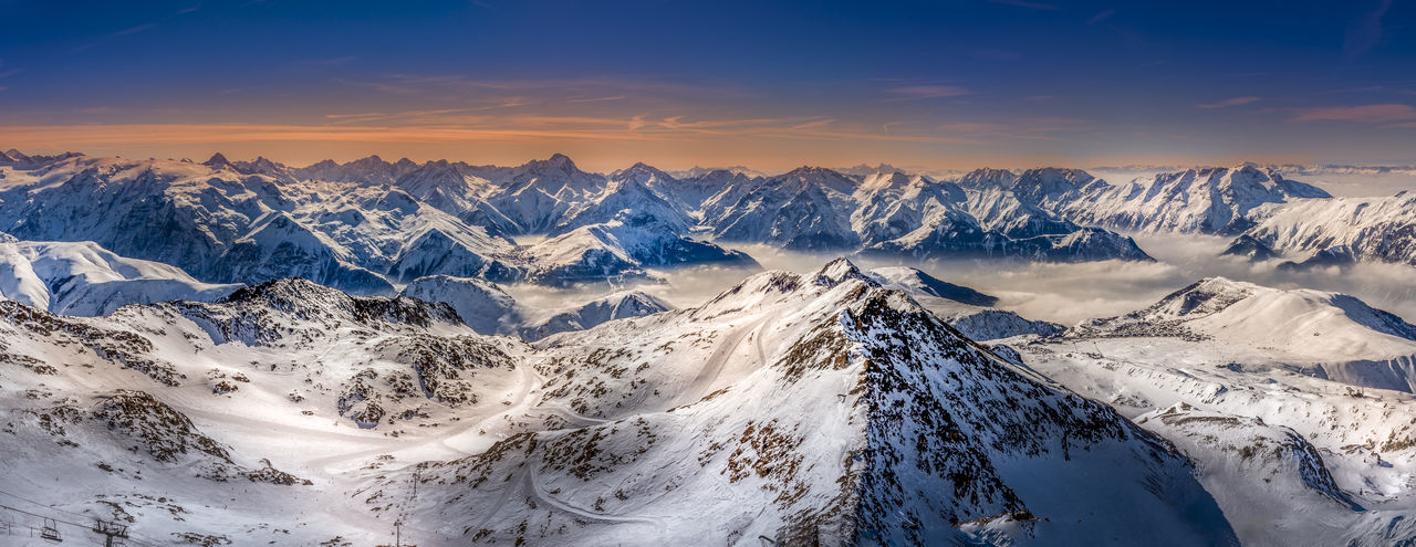 Panoramic Shot Of Snowcapped Mountains Against Sky During Sunset